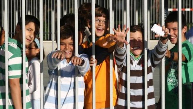 Varios niños saluda en el patio del colegio.