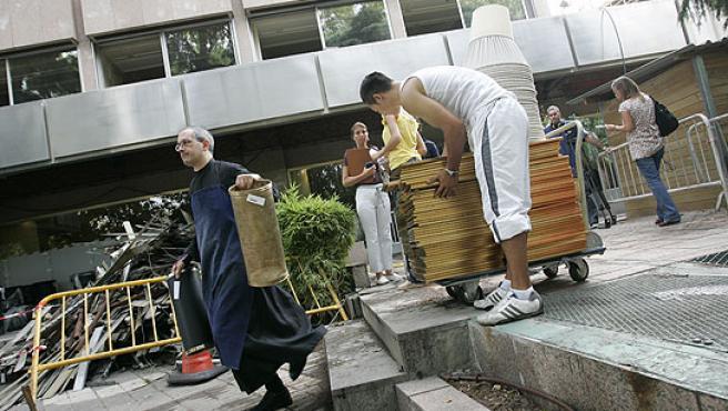 Voluntarios de ONG retirar los muebles cedidos por el hotel. (J. París)