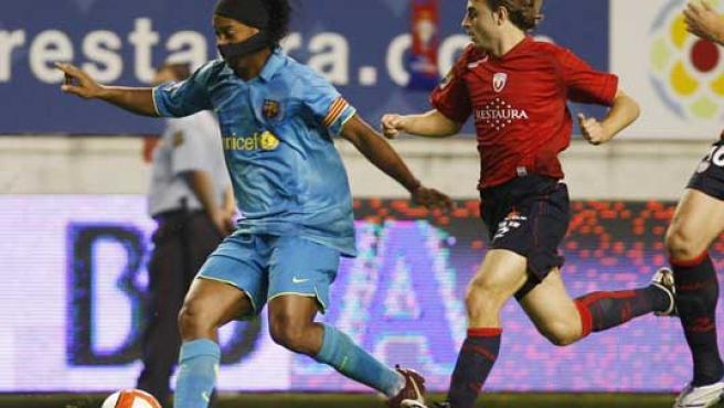 El jugador de Osasuna Hector Font (d), intenta cortar el avance del delantero brasileño del F. C. Barcelona, Ronaldinho, durante el partido correspondiente a la tercera jornada de liga. (EFE)