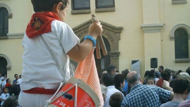 Un niño frente a la Iglesia de San Fermín de Aldapa.