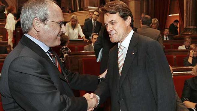 José Montilla y Artur Mas se saludan durante el debate de política territorial en el Parlament.