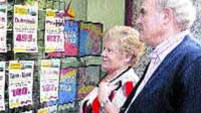 Dos jubilados, ayer, frente al escaparate de una agencia de viajes.(F. Simón)