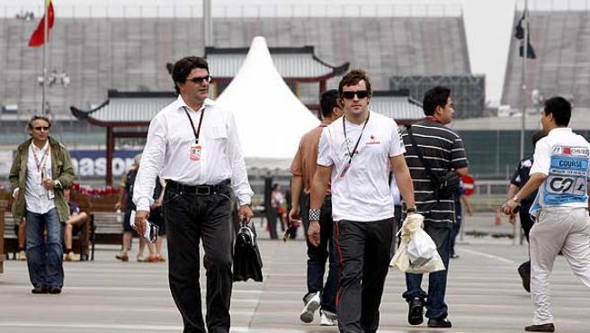 Fernando Alonso y su mánager, Luis García, en Shanghai. (Efe)