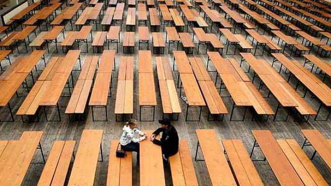 Un pareja dialoga en un banco (Tobias Hase / EFE)