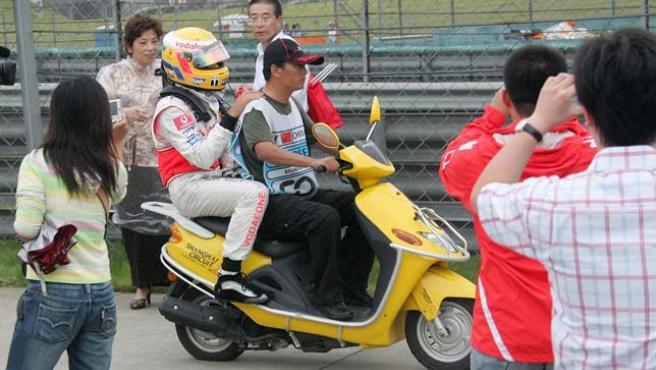 Lewis Hamilton (izq), de la escudería McLaren Mercedes, tras abandonar mientras disputaba el Gran Premio de China (Efe).