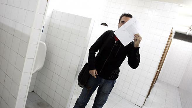Roberto, en el cuarto de baño donde se produjo la agresión, tapándose el rostro con la denuncia. (Jorge París).