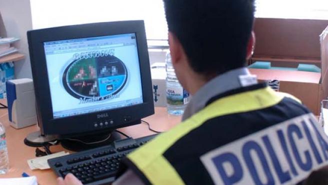 Un policía ante un ordenador con pornografía infantil. (ARCHIVO)