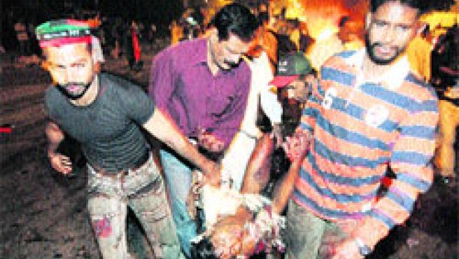Una de las víctimas de ayer es rescatada por varias personas. (AP)
