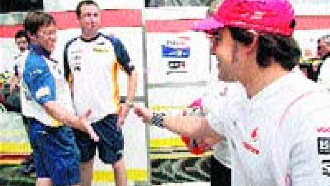 ¿Nos vemos en 2008? La foto es cuanto menos curiosa. Fernando Alonso se detuvo en el motorhome de Renault y saludó a sus amigos de tiempos pasados y... quién sabe si sus mecánicos del año que viene. (EFE)