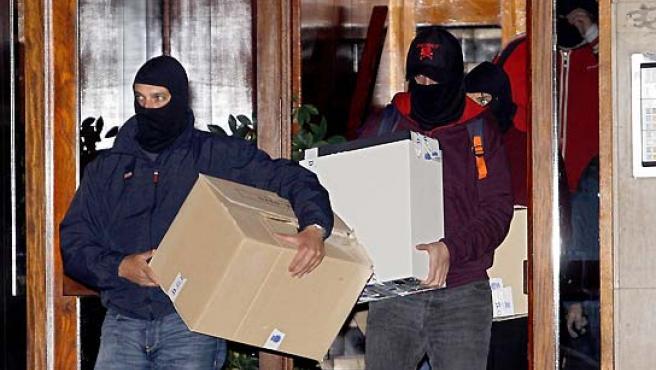Los agentes, con el material incautado esta madrugada en uno de los dos registros realizados en Getxo. (Chema Moya/EFE).