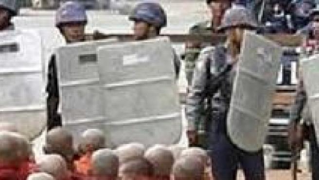 Monjes budistas rezan ante un grupo de policías antidisturbios.