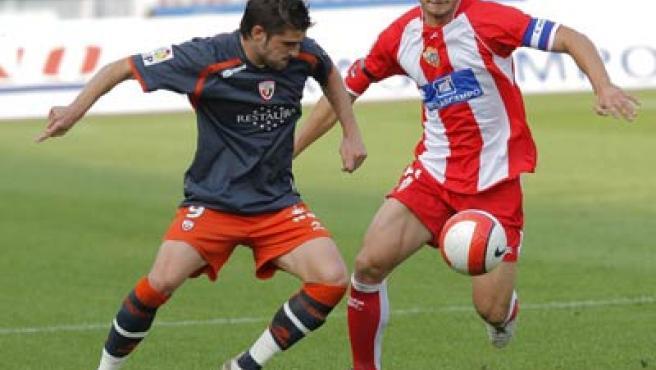El defensa del Almería Carlos Garcia pelea un balón con el delantero Javier García Portillo, de Osasuna.