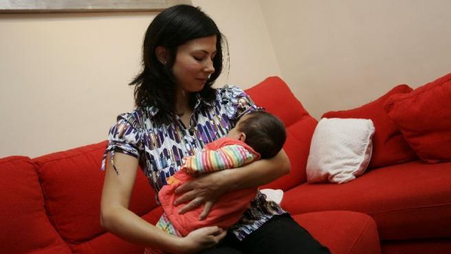 Silvia, acunando a su hija en el salón de su casa.