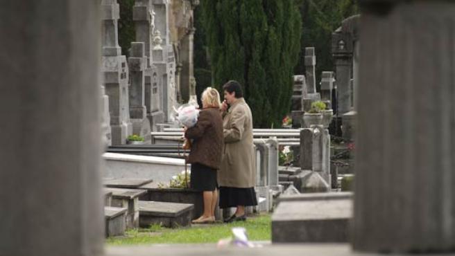 Dos mujeres rezando frente a una tumba en el cementerio de Bilbao, en Derio. (G. ARTAZA).