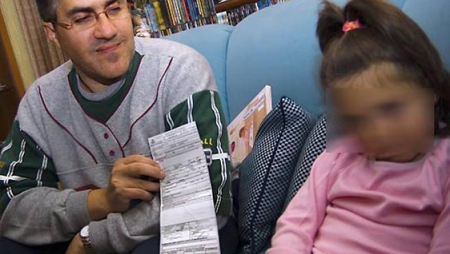 Jesús con su hija de cinco años mostrando los papeles de la multa. (David Rocaberti).