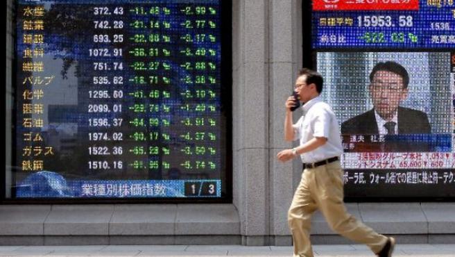 Un hombre pasa por delante de un panel que muestra las cotizaciones del mercado en Tokio.