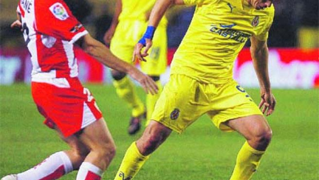 Guille Franco se lleva el balón ante la presión del jugador del Almería Mané.(EFE).