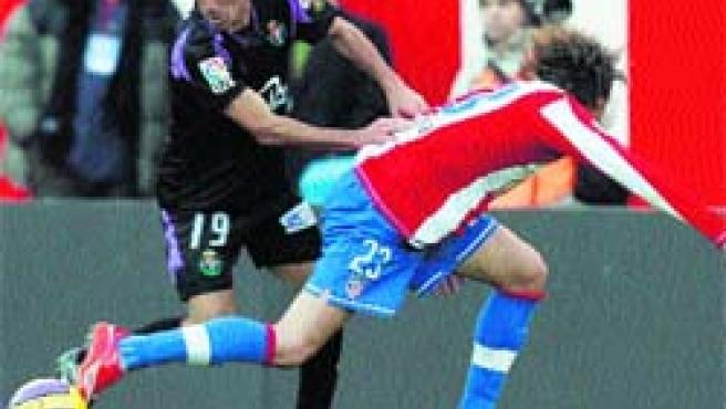 Jonathan Sesma se disputa el balón con Juan Valera en el Vicente Calderón de Madrid. (Juan Carlos Hidalgo / EFE).