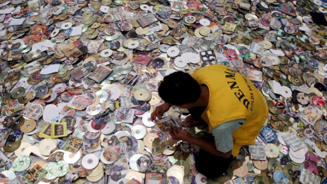 Un agente indonesio mira unos CD y DVD piratas que iban a ser destruidos en Yakarta.