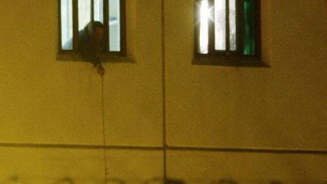Dos presos se comunican, durante el motín, por el exterior de la prisión.