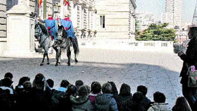 De excursión. Un grupo de escolares observan ayer sentados en el suelo el cambio de guardia. (Antonio Navia)