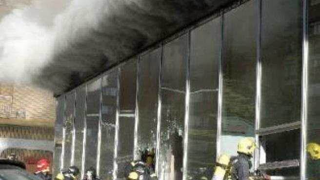 Varios bomberos trabajan en la extinción del fuego declarado en una oficina del INEM de Huesca.