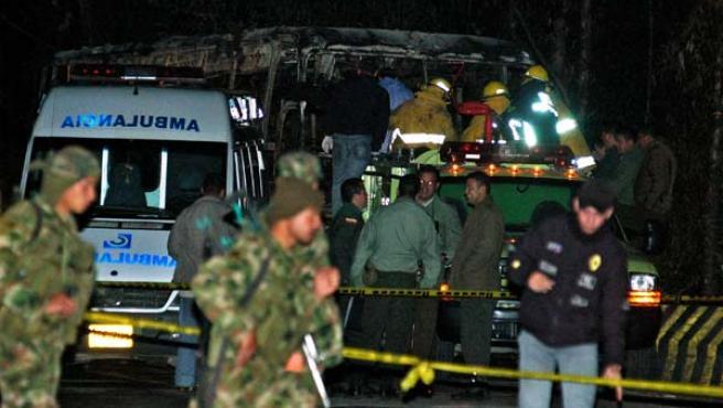 Miembros de la policía, soldados y bomberos rodean el autobús que fue rociado con gasolina e incendiado por unos desconocidos.