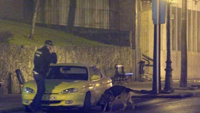 Un artificiero de la Ertzainza, con un perro adiestrado, investiga un vehículo aparcado en las inmediaciones de los juzgados de Sestao. (EFE)