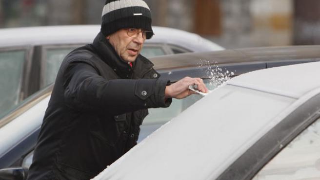 Un hombre limpia el hielo del parabrisas de su coche en Vitoria, ciudad en la que la temperatura mínima ha alcanzado los -6ºC.