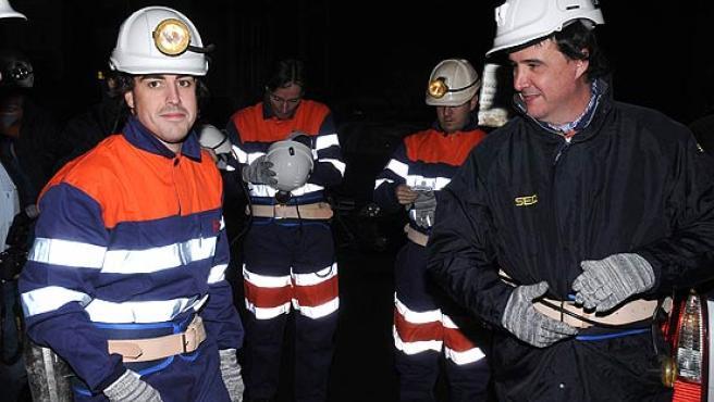 Fernando Alonso (i) y el periodista José Ramón de la Morena (d) en la mina del Pozo de San Nicolás. (Efe)