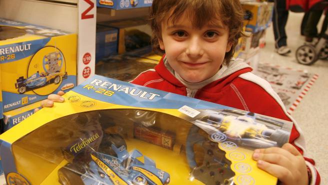 Un niño sostiene en sus manos el coche teledirigido de Fernando Alonso.