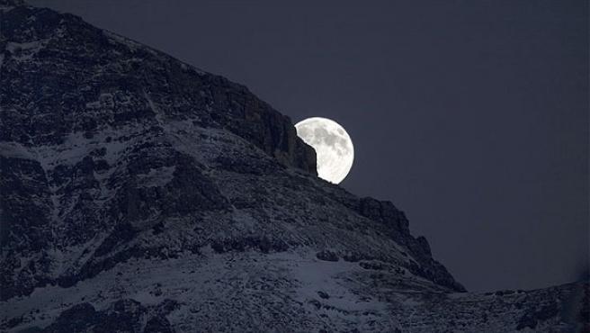 La Luna emerge tras una montaña de las Rocosas, en Alberta, Canadá.