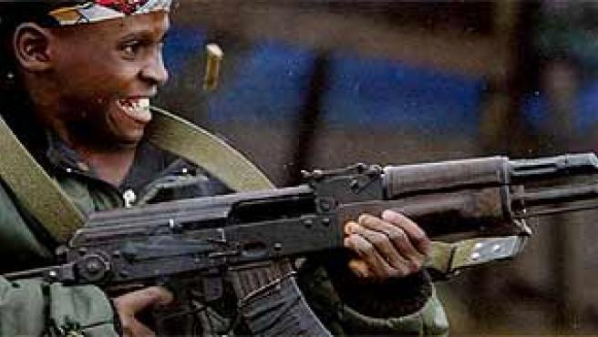 Un niño disparando con un fusil en Monrovia, Liberia, en julio de 2003. (Nic Bothma. / Efe)