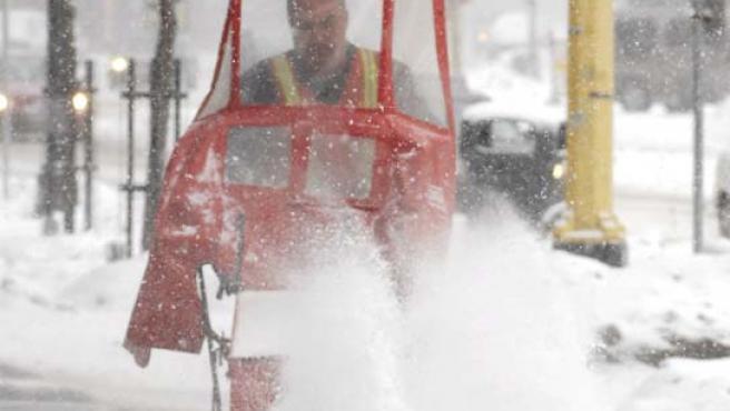 Un operario limpia el domingo una calle cubierta por la nieve en Minneapolis. (EFE)