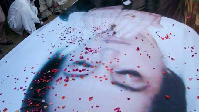 Partidarios de la líder opositora asesinada Benazir Bhutto depositan pétalos de rosa sobre su retrato en Peshawar, Pakistán.