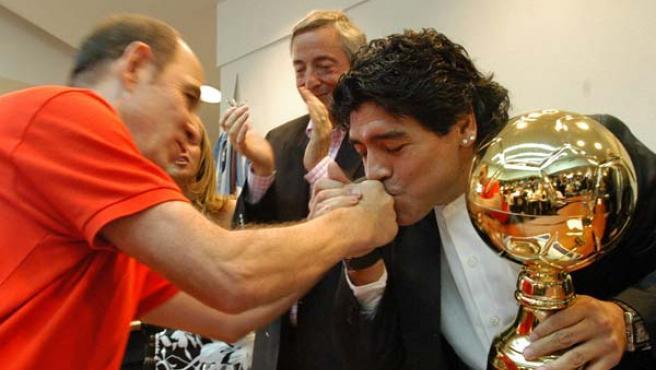 El ex futbolista Diego Maradona besa la mano a Ricardo Bochini. (EFE)