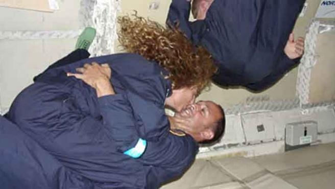 Dos astronautas se besan en el espacio.