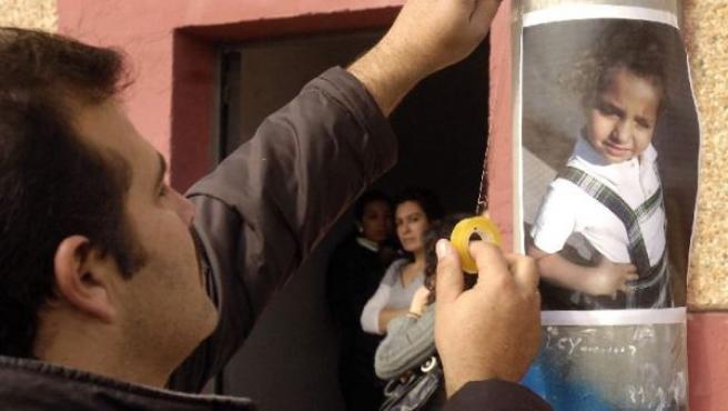 Un vecino coloca un cartel con la foto de la pequeña desaparecida. (Foto: Iván Quintero / EFE)