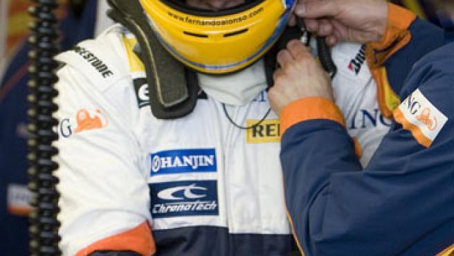 Fernando Alonso se prepara antes de introducirse en su monoplaza, en el box del equipo Renault.