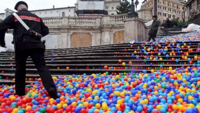 Un policía se abre paso entre las miles de pelotas de colores en la escalinata de la Plaza de España de Roma. (Di Meo-Percossi / EFE)