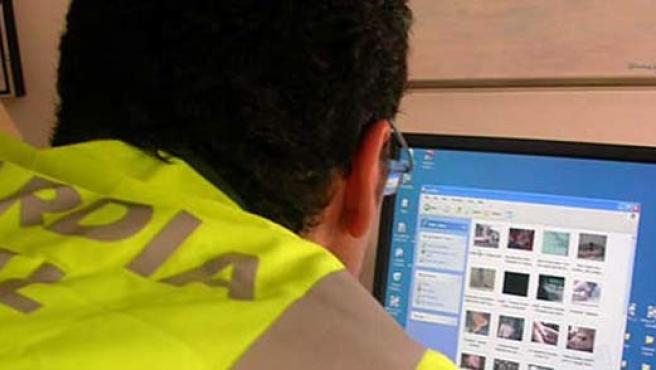 Un agente revisa el contenido de un ordenador.