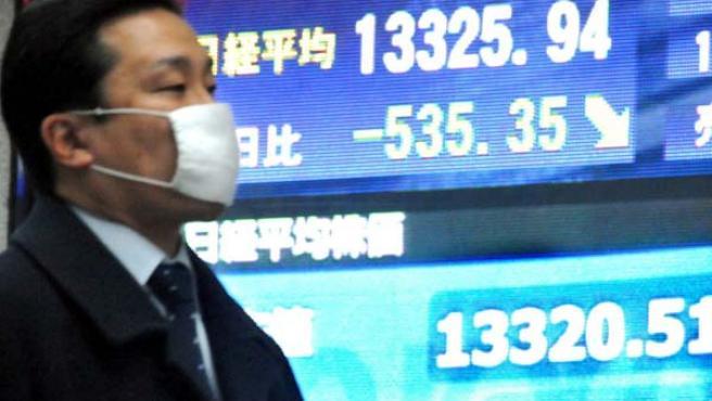 Un viandante pasa delante de una pantalla que muestra el índice Nikkei de la bolsa de Tokio. (EFE)