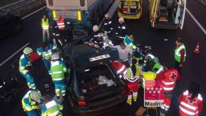 Bomberos y miembros del SUMMA atienden a los heridos en un accidente ocurrido en la Autovía de Extremadura en el que una mujer de más de 60 años ha muerto. (EFE).