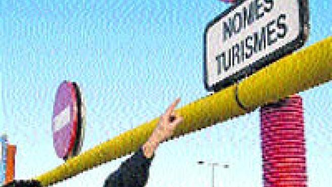 Una barra no deixa passar vehicles que no siguin turismes. A dalt, uns operaris canviant ahir els pilons fixes per uns altres de mòbils (Eros Albarrán).