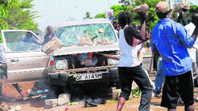 Varis manifestantes apedreaban ayer un vehículo oficial en la ciudad de Kisumu, en el oeste de Kenia, tras la muerte del diputado opositor. (EFE)