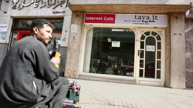 Un limpiabotas trabaja frente a un cibercafé en el centro de El Cairo.