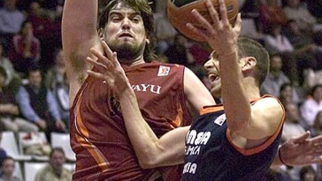 El base valencianista Albert Oliver intenta entrar a canasta ante la oposición del jugador de Akasvayu Marc Gasol (EFE).