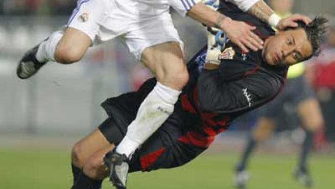 El defensa del Real Madrid Sergio Ramos disputa un balón con el portero brasileño del Almería Diego Alves.
