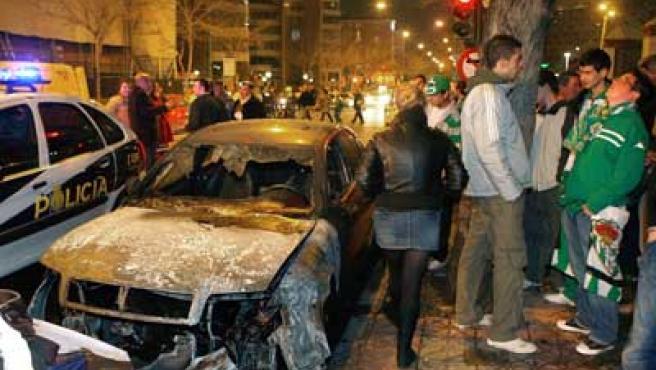 Uno de los coches quemados tras los incidentes entre aficionadoas del Real Betis y del Deportivo de La Coruña.
