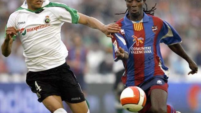 El centrocampista ghanés del Levante, Mustapha Riga (d) controla un balón ante la presión del defensa Ezequiel Garay. (EFE)